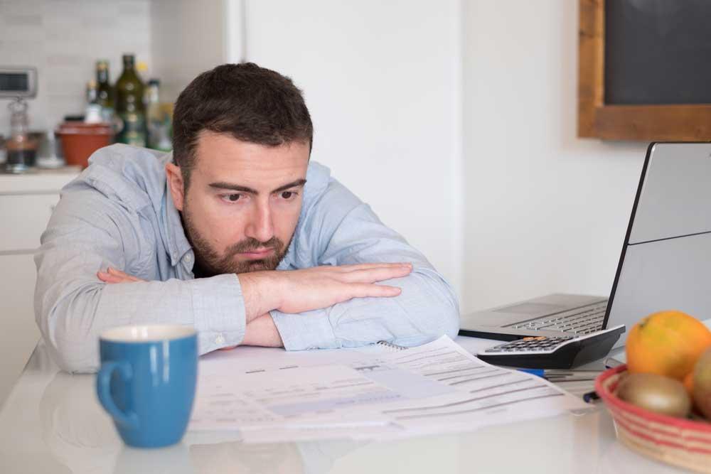 Sad man gone bankrupt sitting at desk by laptop