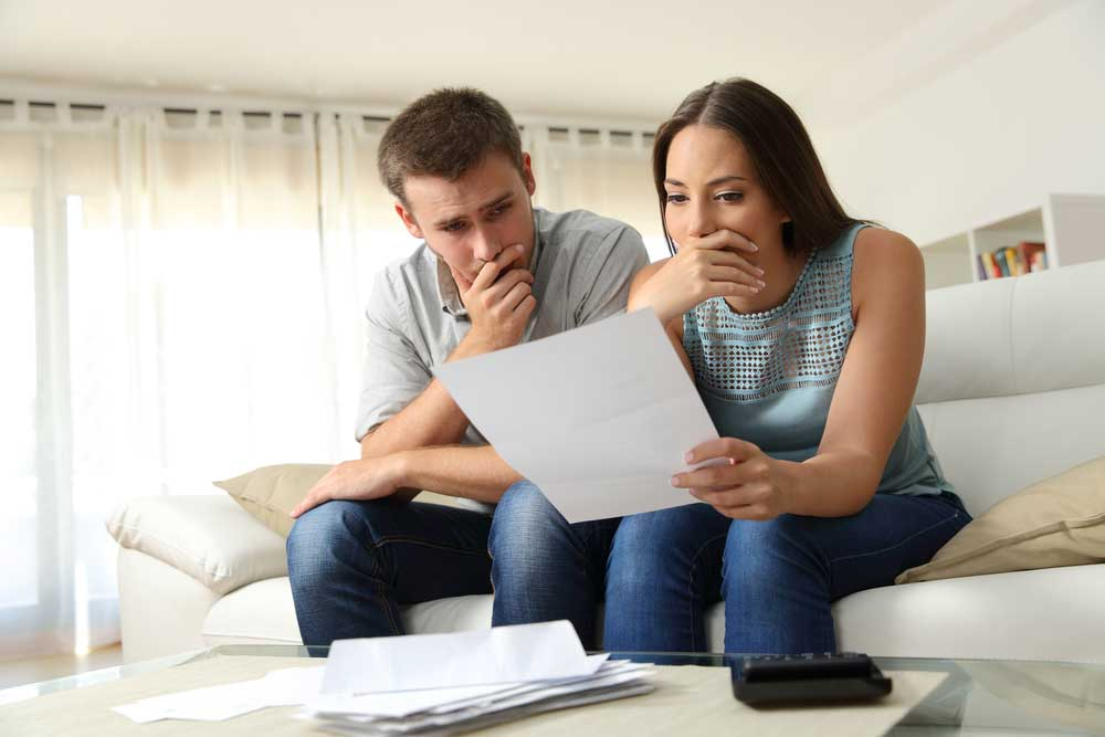 Couple sitting in couch worried about financial papers