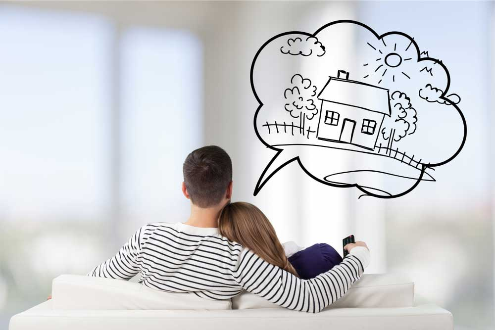 Couple sitting in couch dreaming of buying a new home