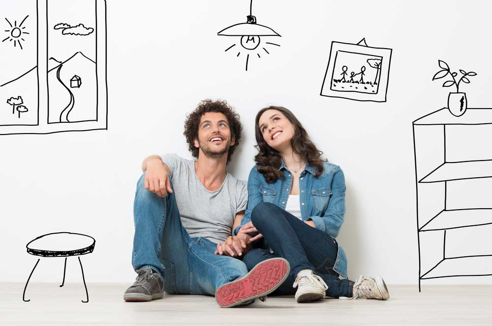 Young couple sitting on the floor dreaming of buying a home