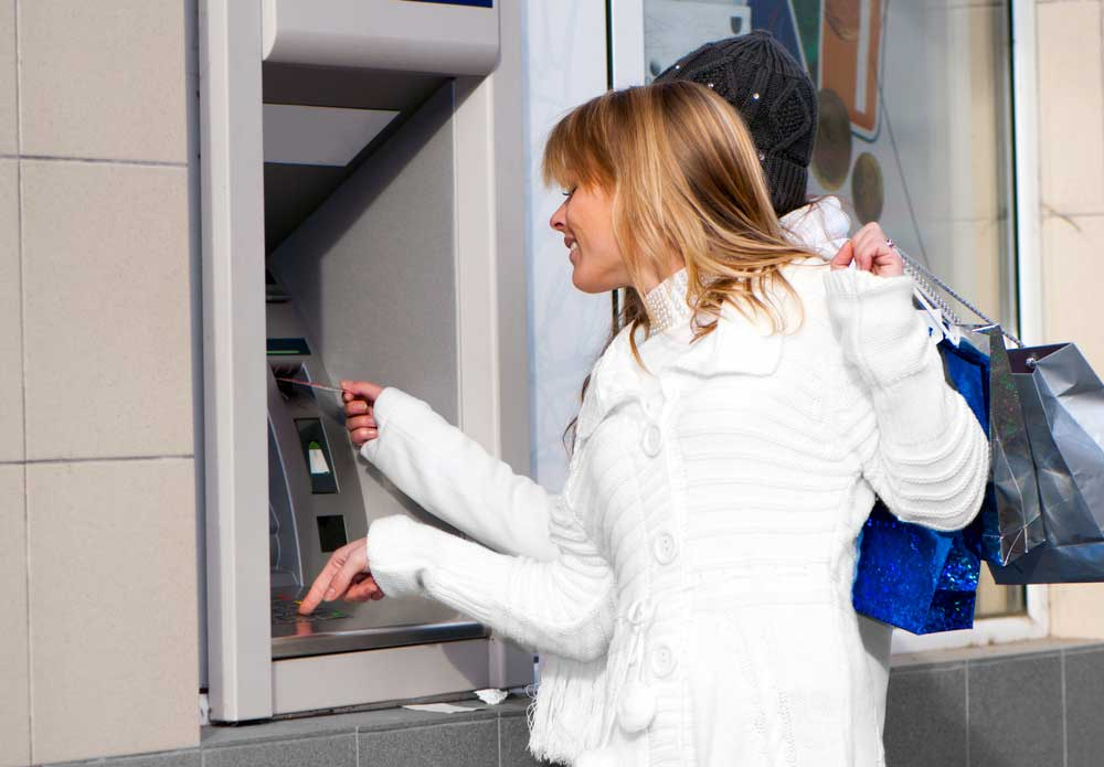 Woman placing her credit card into an ATM