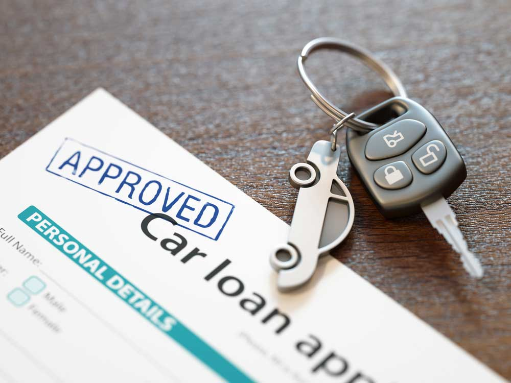 Approved car loan application and car keys on a table