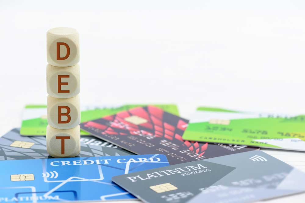"A number of credit cards and dices forming the word ""debt"""