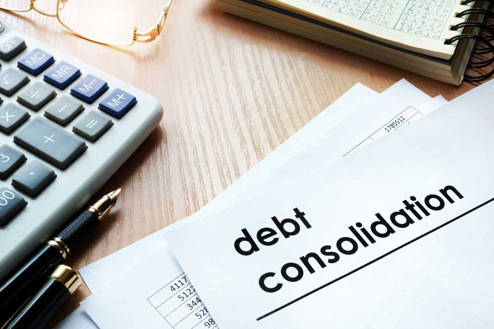 Desk with calculator and debt consolidation paper