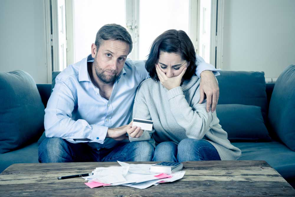 Sad couple sitting in couch looking at financial papers