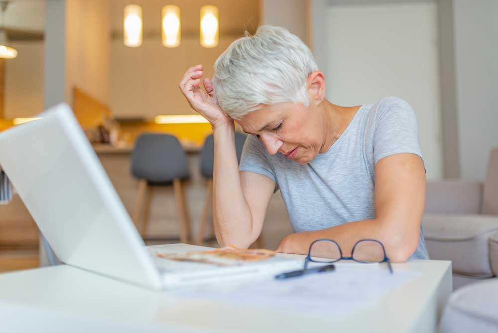 Worried woman sitting in front of laptop