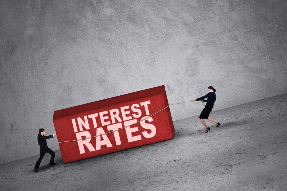 "Man and woman dragging and pulling a big box with the words ""Interest rates"""