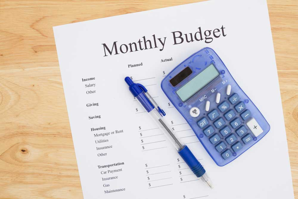 Pen, calculator, and print of monthly budget on a table
