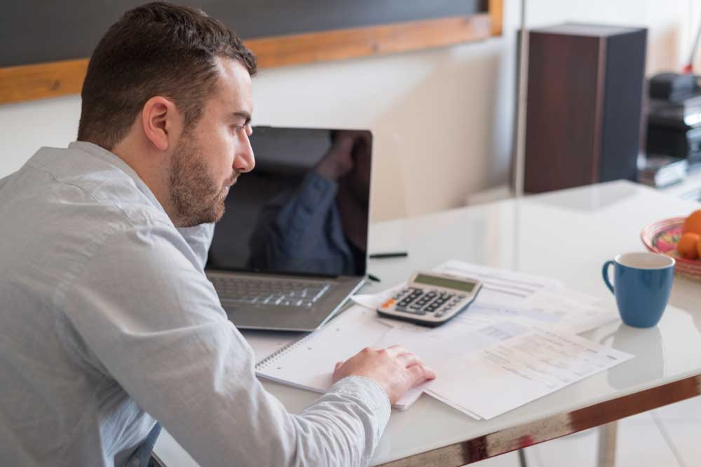 Man sitting at desk going though his financials