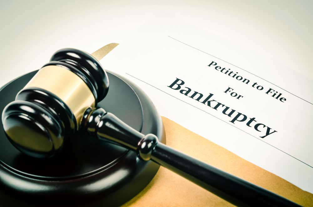 """Document with the title """"Petition to file for bankruptcy"""" on a table"""
