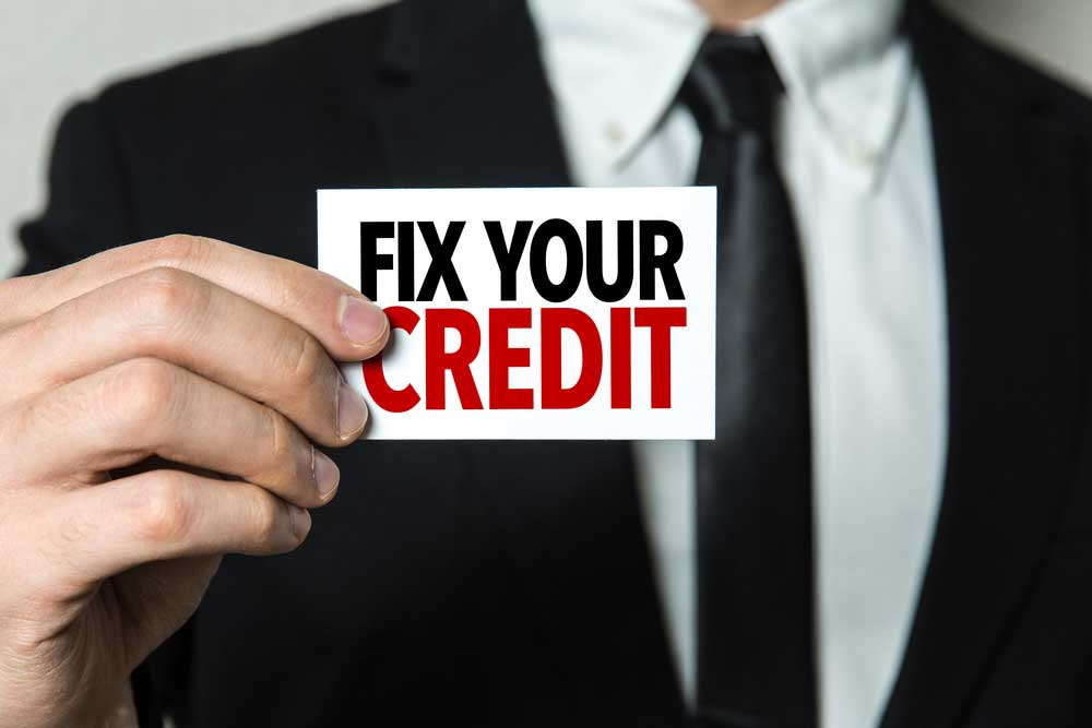 "Business man holding a card with the text ""Fix Your Credit"""