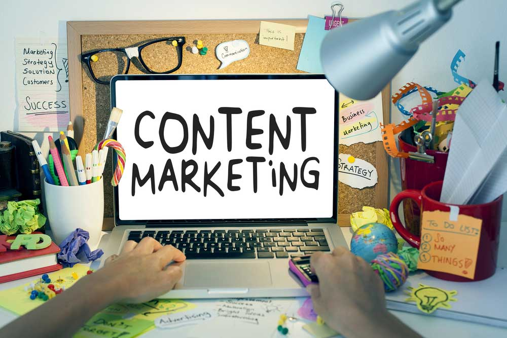 """Office desk with the word """"Content Marketing"""" on a laptop"""