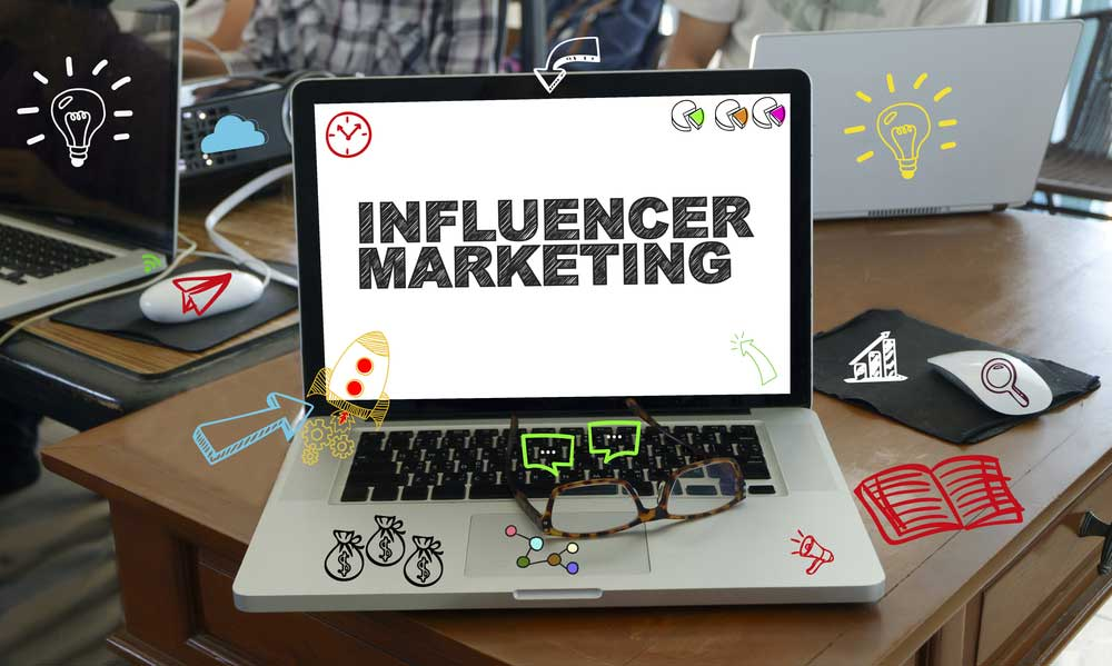 """Laptop on office desk with the words """"Influencer Marketing"""" on the screen"""