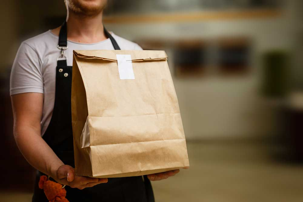 Man delivering Just-Eat take-away fast food in a brown paper bag.