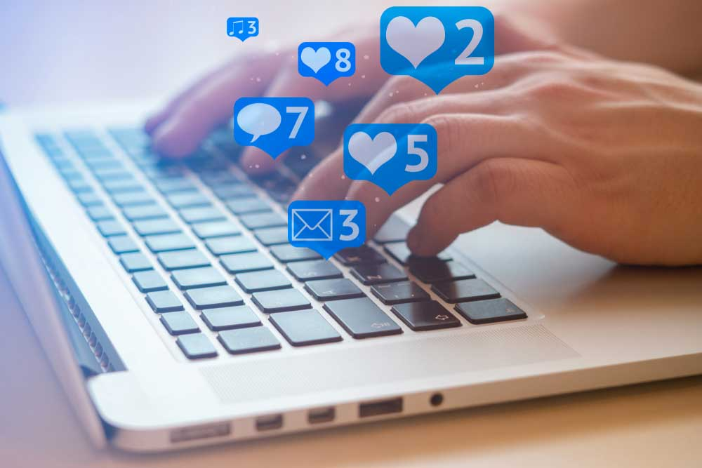 Hands on laptop with various social media icons showing