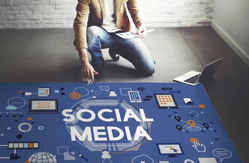 Large social media sign on the floor with man and laptop next to it.